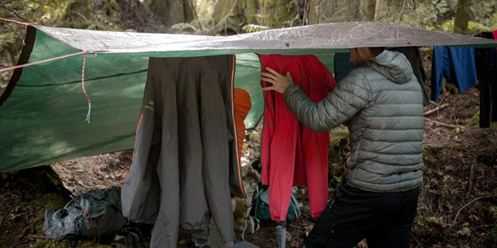 a man is drying clothes while camping in the rain under a shelter